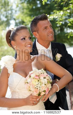 Portrait of happy young couple on wedding-day. Outdoor photo.