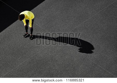 Runner In Yellow Sportswear Resting After Running. Jogging Man Taking A Break During Training Outdoo