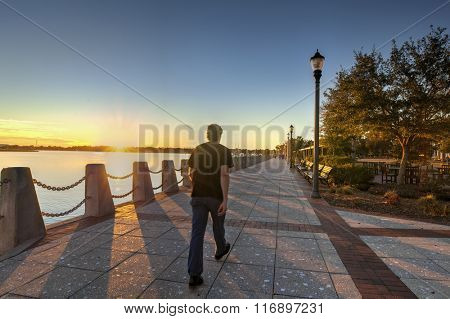 Waterfront park at sunset in Beaufort, South Carolina, man walking by with motion blur