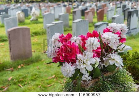 Tombstones On A Graveyard In Fall With Flowers In The Foreground