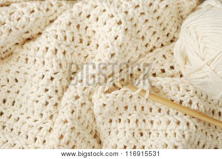 Crochet project - partially finished.  Natural, pure, organic cotton yarn being worked into a pattern of double crochet stitches using a bamboo hook.