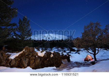 rock formation 'sciara' and lighting tent in the snow of Etna Park under starry sky, Sicily