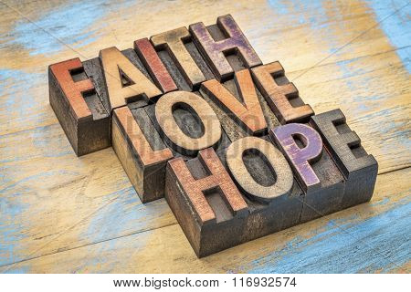 faith, love and hope - words in vintage letterpress wood type stained by color inks against painted wood