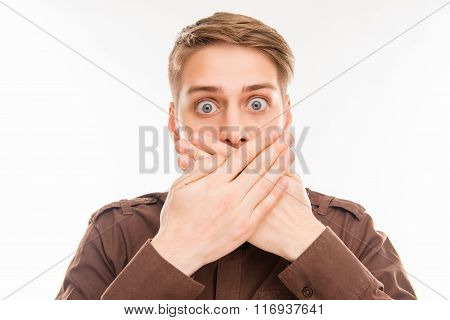 Close Up Portrait Of Shocked Young Man Closing His Mouth With Hand