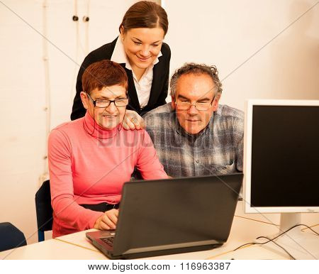 Young Woman Teaching Elderly Couple Of Computer Skills. Intergenerational Transfer Of Knowledge.