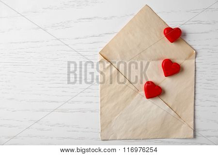 Blank open envelope with small hearts on wooden background