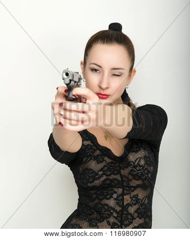 sexy young woman in a black lace bodysuit with braided hair is holding a gun. on the feet thick blac