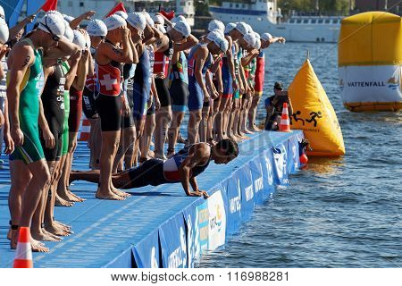 STOCKHOLM - AUG 22 2015: Group of male swimming competitors in colorful swimsuits waiting for the start signal in the Mens's ITU World Triathlon series event August 22 2015 in Stockholm Sweden