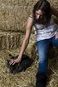 Young women sitting on bales of straw petting her pet cat poster