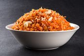 tasty gajar halwa or gajar ka halwa made up or fresh carrot, sugar and milk. decorated with almond or badam, cashewnuts and pistachios, favourite north indian dessert usually served in weddings poster