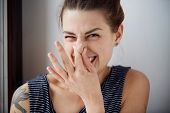 Female gesture smells bad. Headshot woman pinches nose with fingers hands looks with disgust something stinks bad smell situation. Human face expression body language reaction poster