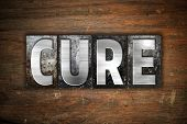 """The word """"Cure"""" written in vintage metal letterpress type on an aged wooden background. poster"""