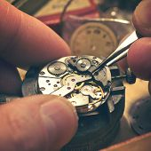 Working On A Mechanical Watch. A watch makers work top. The inside workings of a vintage mechanical watch. poster