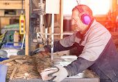 Strong man carpenter using table saw for cutting wood at workshop - Woodworker working hard in Switzerland mountains - Industrial work concept - Soft warm filtered look with artificial sunlight poster