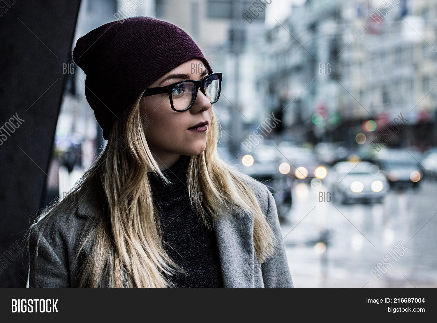 0046a3fc4635 Perfect city style. Portrait of beautiful hipster girl in stylish coat  looking away while standing