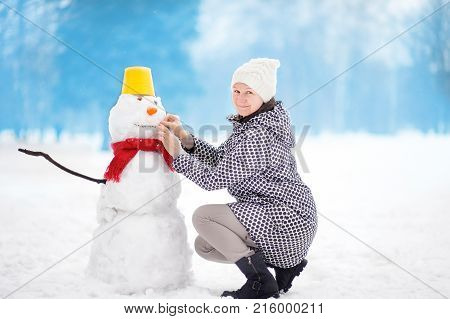Portrait of smiling beautiful middle age/mature/older female building snowman in snowy park. Active outdoors family leisure in winter. People during stroll in a snowy winter park