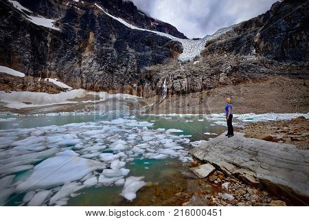 Woman by glacier lake. Hiking to waterfall from Angel Glacer to the lake at the bottom of Mount Edith Cavell in Jasper National Park. Alberta. Canada.