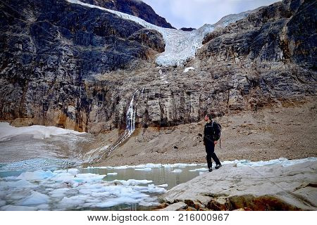Hiking in Canadian Rockies. Man hiker by a moraine lake and Angel glacier at Mount Edith Cavell. Jasper National Park. Alberta. Canada.