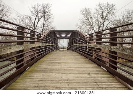Crossing Over. Wood and metal bridge with diminishing perspective crosses over a stream in Sterling State Park on the shores of Lake Erie in Monroe, Michigan.