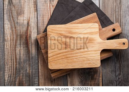 Oak cutting board over towel on wooden kitchen table. Top view.