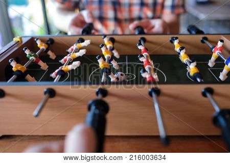 Man playing table football soccer game close up with his friends. Control the players.