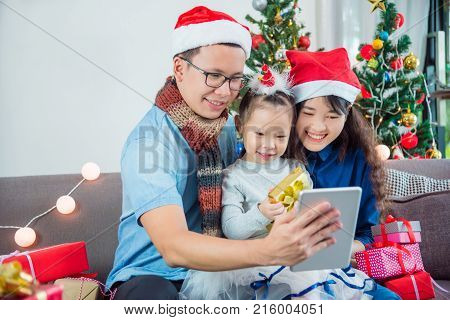 Asian family using video call by tablet computer on Christmas holiday