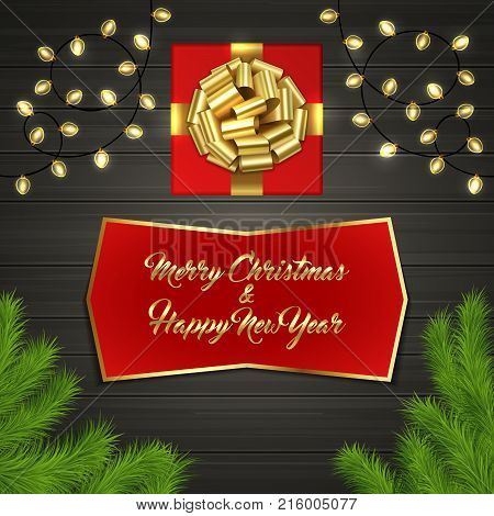 Christmas card with Cristmas fir tree branches, red square gift box with gold ribbon bow, garland on black wooden board. Greeting text Merry Chrismas and Happy New Year on red label with gold frame