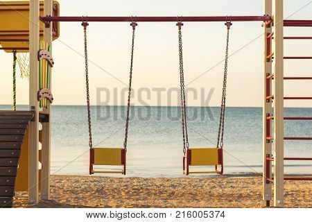 Swings on chains for two on the background of evening sunset sea. The concept of a romantic evening for lovers.