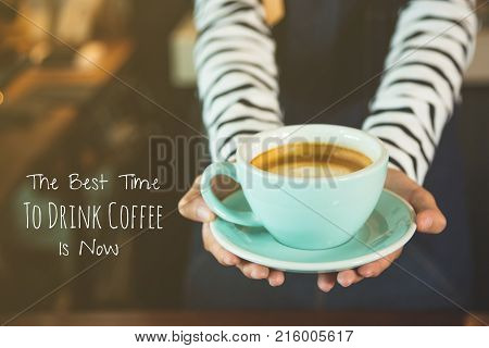 Coffee quote : The best time to drink coffee is now . Quote with hands of a woman holding coffee cup.