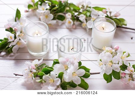 Apple tree flowers and three candles on white wooden background. Selective focus is on candle.