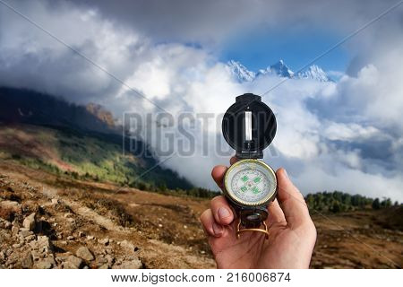 Traveler with compass seeking a right way in the mountains during Hike. Navigation concept in explore travel.