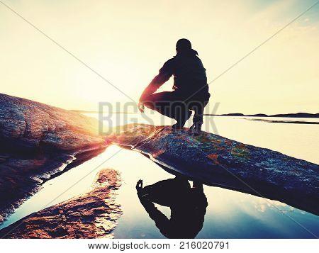 Evening Island Coastline. Hiker Relaxing On Coast  And Enjoying Colorful Sunset At Horizon.