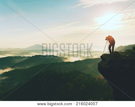 Nature Photographer In The Action.  Man Silhouette Above A Misty Clouds,