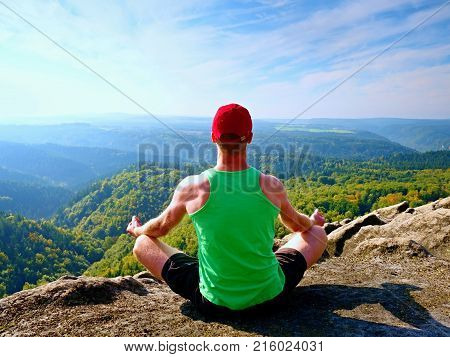 Man Sitting On The Top Of The Mountain In Yoga Pose. Exercise Yoga On The Edge With A Breathtaking V