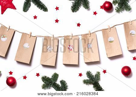 Handmade Tinkered Advent Calendar With Paper Bags And Stickers With Fir Branches And Red Stars On Wh