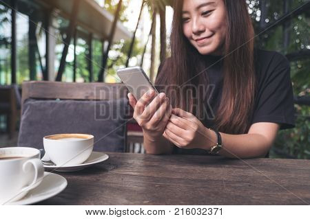 Closeup image of a beautiful Asian woman with smiley face holding and using smart phone with coffee cups on wooden table in cafe