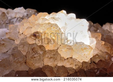 Closeup photograph of quartz stone lit from inside on a black background. Natural phenomenon.
