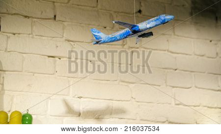 Homemade airplane in the room. On the background of stone wall hanging toy airplane on a rope, the concept of hand made.