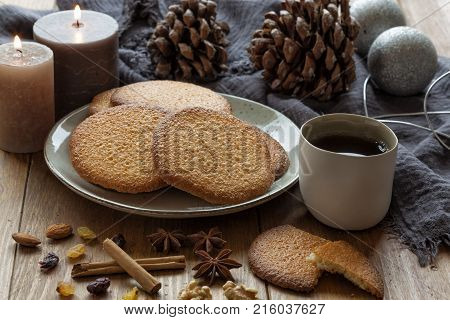 Christmas with hot tea cookies cinnamon aniseed candles and pine cones.