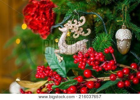 Toy golden deer on the Christmas tree. Christmas tree decorated with toys.The concept of Christmas