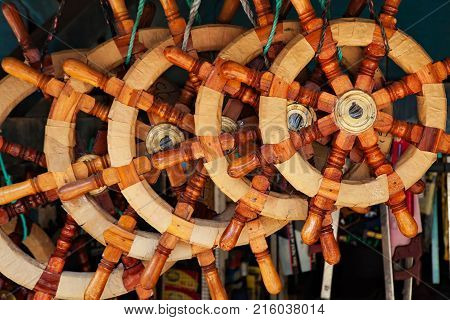 Market stall with many varieties of traditional old style wooden steering wheels for ships in Jakarta street shop near sea harbour. Sea yachts equipment retail in Indonesia. Asian travel background.