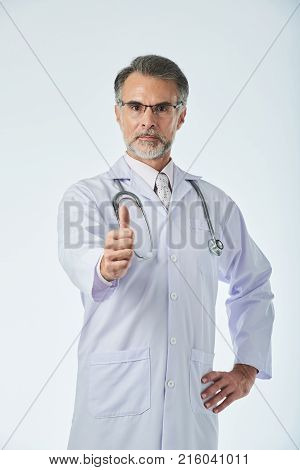 Portrait of mature general practitioner showing thumbs-up poster