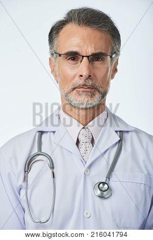 Portrait of unsmiling mature general practitioner in glasses
