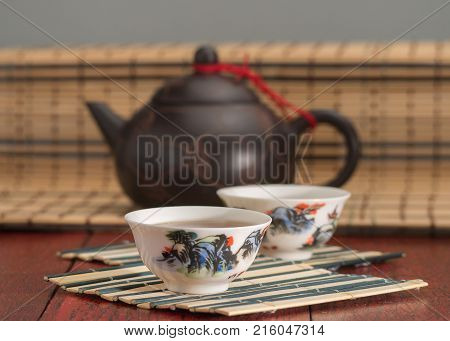 Chinese brown ceramic teapot on bamboo mat. Two white tea cups on a little wooden color mat. Black tea in tea porcelans cup. Red table background