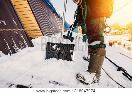 Cleaning roofs of buildings from snow ice in the winter with a shovel.