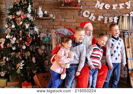 Lovely little male and female children joyfully sing Christmas songs carols, together with father they happy, waving their hands on camera in anticipation of miracle New Years Eve cozy, decorated room large floor lamp, walls which posters hang, high- Unde