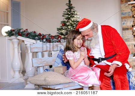 Pretty princess dressed in rosy frock whirling near Father Christmas. Funny Santa Claus playing with little female child on Christmas party. Concept of celebrating Noel with invited Father Christmas.