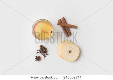 top view of apple cider composition with spices and pear slices on white tabletop