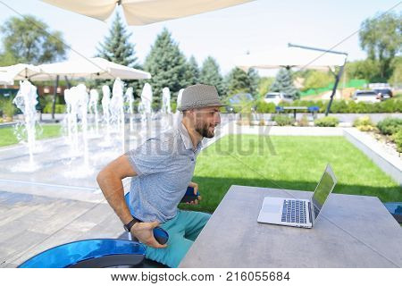 Skilled actuary working with laptop and documents at cafe table.