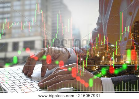 Double exposure of businessman using the laptop with cityscape and stock market or financial graph for financial investment concept on blurred building background Business investment and trading concept.